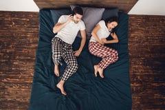 Vue supérieure L'homme alarmé dans des pyjamas sonne le téléphone, à côté de la belle fille qui donne naissance photographie stock