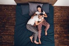 Vue supérieure L'homme calme dans des ses pyjamas a étendu sa tête sur le ventre du ` s de femme enceinte, se trouvant pas sur le images stock