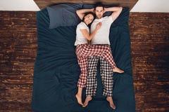 Vue supérieure La belle jeune femme se trouve à côté de l'homme bel Poses de sommeil pour des couples photos stock
