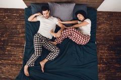 Vue supérieure La jeune belle femme dans le pyjama pousse l'homme de sommeil adulte du lit photographie stock