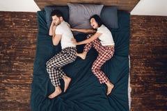 Vue supérieure La jeune belle femme dans le pyjama pousse l'homme de sommeil adulte du lit photos stock