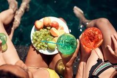 Vue supérieure Les filles dans des maillots de bain mangent des fruits et boivent des cocktails dans la piscine dans l'été Images libres de droits