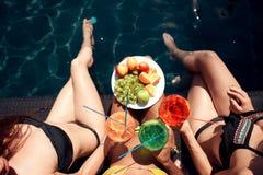 Vue supérieure Les filles dans des maillots de bain mangent des fruits et les cocktails de boissons boit dans la piscine dans l'é Photos stock