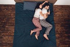 Vue supérieure Les jeunes couples dans des sommeils de pyjamas se ferment ensemble sur le lit à la maison photographie stock libre de droits