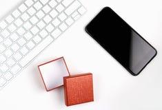 Vue supérieure, lieu de travail moderne avec le téléphone intelligent et boîte-cadeau avec le clavier placé sur un fond blanc en  Photographie stock