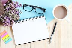 Vue supérieure ou configuration plate de papier ouvert de carnet, de bouquet des fleurs sauvages sèches et de tasse de café sur l Photo stock