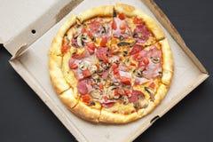 Vue supérieure, pizza fraîchement cuite au four dans une boîte en carton sur le fond foncé D'en haut, photographie stock libre de droits