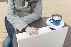 Vue supérieure, plan rapproché d'ordinateur portable avec la tasse de café d'art et main femelle sur le clavier, table au café ex photographie stock libre de droits