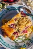 Vue supérieure sur la partie du gâteau de cerise avec les fleurs et la brindille jaunes de romarin Photographie stock libre de droits