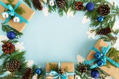 Vue supérieure sur le cadre des décorations de Noël, des boîte-cadeau, des branches de sapin et des cônes de pin sur le fond bleu Photographie stock