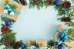 Vue supérieure sur le cadre des décorations de Noël, des boîte-cadeau, des branches de sapin et des cônes de pin sur le fond bleu Photos libres de droits