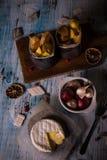 Vue supérieure sur le fromage de camembert Melted sur le conseil en bois aux oignons et aux stripps frits de pomme de terre photo stock