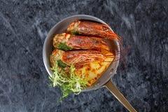 Vue supérieure sur les crevettes grillées delecious dans la petite casserole sur la table de marbre image stock
