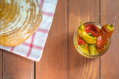 Vue supérieure sur les poivrons de piments marinés ouverts dans le pot en verre avec du pain Image libre de droits