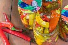 Vue supérieure sur les poivrons de piments marinés ouverts dans le pot en verre avec frais Photographie stock libre de droits