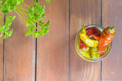 Vue supérieure sur les poivrons de piments marinés ouverts dans le pot en verre avec Parsle Photo stock
