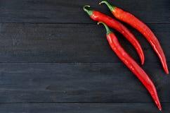 Vue supérieure sur trois poivrons de piment d'un rouge ardent au-dessus de fond en bois noir avec l'espace de copie Vue générale Photos stock