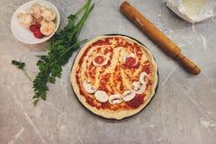 Vue supérieure sur une pizza partiellement cuite avec les produits présentés sous forme de sourire image stock
