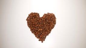 VUE SUPÉRIEURE : Symbole de coeur des grains de café sur la table blanche Photo stock
