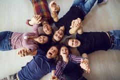 Vue supérieure Un groupe d'amis rient le mensonge sur le plancher Image libre de droits