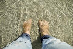 Vue sup?rieure des personnes regardant vers le bas des pieds mis sous le sable et la mer photo libre de droits