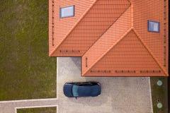 Vue sup?rieure a?rienne de toit de bardeau en m?tal de maison avec les fen?tres de grenier et la voiture noire sur la cour pav?e photographie stock
