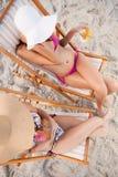 Vue supplémentaire des jeunes femmes s'asseyant sur la plage Image libre de droits