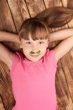 Vue supérieure d'une petite fille se trouvant dessus de retour Image stock