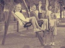 Vue sur des enfants balançant ensemble sur le terrain de jeu des enfants Image stock