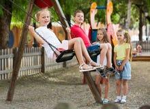 Vue sur des enfants balançant ensemble sur le terrain de jeu du ` s d'enfants Photographie stock libre de droits