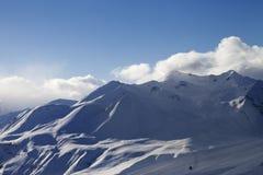 Vue sur des montagnes de pente et de lumière du soleil de ski dans la soirée Photo libre de droits