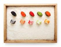 Vue sur des petits pains de sushi et gunkan supérieurs dans le cadre en bois sur le fond de riz blanc et l'espace de copie de tex Photographie stock libre de droits