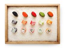 Vue sur des petits pains de sushi et gunkan supérieurs dans le cadre en bois sur le fond de riz blanc et l'espace de copie de tex Photo stock