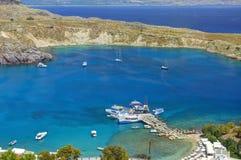 Vue sur la belle baie de Lindos avec les bateaux blancs sur l'eau, bateaux de croisière Plage de sable avec des touristes de nata Photos libres de droits
