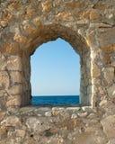 Vue sur la mer de l'hublot de forteresse photos stock