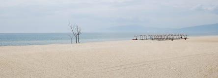 Vue sur la plage sablonneuse sans fin, parapluies, lits pliants en Grèce Photos stock