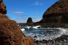 Vue sur la roche de pupitre d'une plage en pierre noire au cap Schank sur la péninsule de Mornington, Australie photos stock