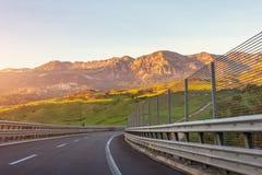 Vue sur la route et tourner dans les collines, montagnes le soir au coucher du soleil, voyage de voyage image libre de droits