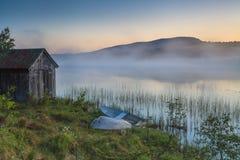Vue sur le lac brumeux avec des bateaux sur le rivage Images stock