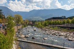 Vue sur le passant de rivière avec la promenade, végétation et autour des bâtiments en Meran Province Bolzano, Tyrol du sud, Ital images libres de droits