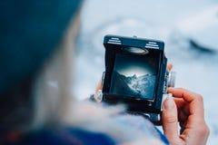 Vue sur le paysage de montagne par le viseur de la vieille photo de caméra Le photographe de la vieille école prend a images stock