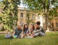 Vue sur les étudiants gais s'asseyant sur l'herbe le jour ensoleillé Images stock