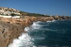 Vue sur roches et vague déferlante de côte avec des villas Photos libres de droits