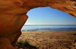Vue sur un bord de la mer arénacé d'une caverne Image libre de droits