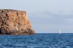 Vue sur une grande roche et un voilier en mer Image libre de droits