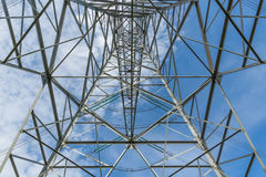 Vue symétriquement inférieure de pylône de l'électricité contre un ciel bleu Images libres de droits