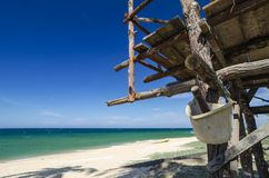 Vue tropicale de mer sous la hutte en bois au jour ensoleillé ciel arénacé bleu de plage Images stock