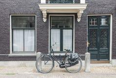 Vue typique de rue d'Amsterdam aux Pays-Bas avec de vieilles portes et fenêtres et bicyclette de cru photographie stock libre de droits