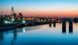 Vue urbaine de nuit de port fluvial avec des grues Image stock