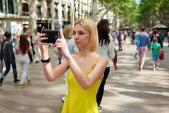 Vue urbaine de photographie de jolie jeune femme avec l'appareil-photo de téléphone portable pendant le voyage d'été Image stock